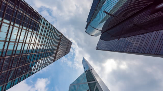 4k time lapse : vertical view of high rise skyscraper buildings in hong kong city. modern city business district background - skyscraper stock videos & royalty-free footage