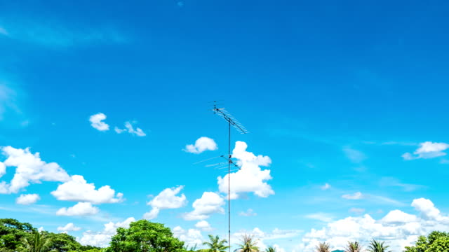 time lapse video of aerial television antenna with cloud moving and blue sky - television aerial stock videos and b-roll footage