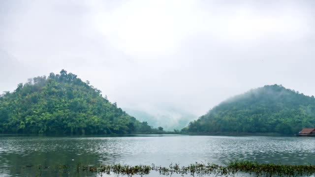 vídeos de stock e filmes b-roll de time lapse video of beautiful lake in front of twin mountains with fog and cloudy sky. - vinheta