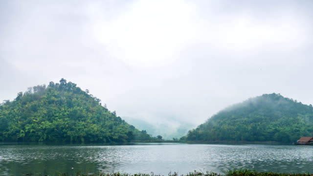 vídeos de stock, filmes e b-roll de lapso de tempo vídeo do belo lago na frente de montanhas gêmeas com céu nublado e névoa. - vinheta