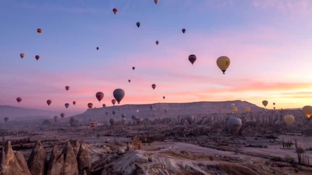 time lapse  video of hot air balloons flying in red and rose valley in goreme in cappadocia in turkey - hot air balloon stock videos & royalty-free footage