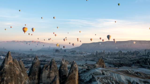 vídeos de stock, filmes e b-roll de lapso de tempo vídeo de balões de ar quente voar no vale vermelho e rosa em göreme, na capadócia, na turquia - capadócia