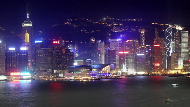 time lapse view across victoria harbour of hong kong convention and exhibition centre in wan chai north skyline at night / hong kong - wan chai stock videos & royalty-free footage