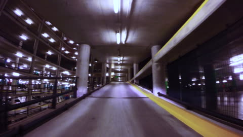 time lapse view driving through a huge concrete parking with ramps at night. - 階点の映像素材/bロール