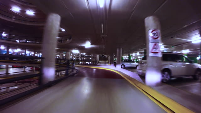 Time lapse view driving through a huge concrete parking with ramps at night.