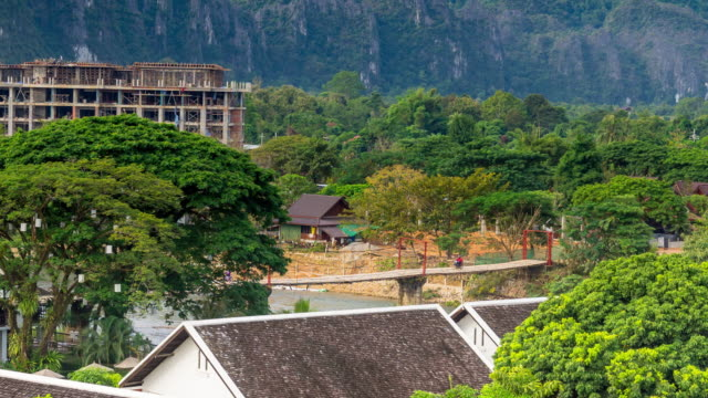 4K Time lapse : View from traditional long tail boat and wood bridge on the Nam Song River. Vang Vieng Laos.