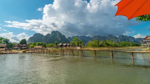 4K tidsfördröjning: utsikt från traditionella lång svans båt och trä bro på Nam Song-floden. Vang Vieng Laos.