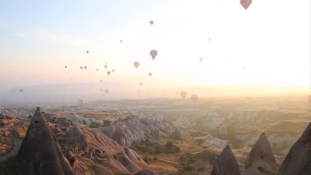Time lapse view of balloons rising above desert landscape