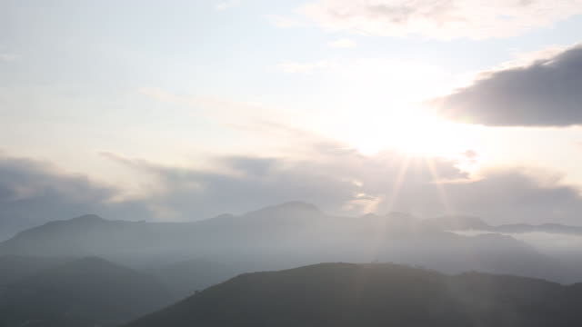 Time lapse view of clouds and setting sun behind hills