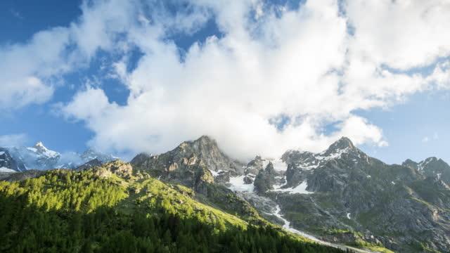 stockvideo's en b-roll-footage met tijd lapse weergave van wolken en zonsopgang boven groen bos - stilstaande camera