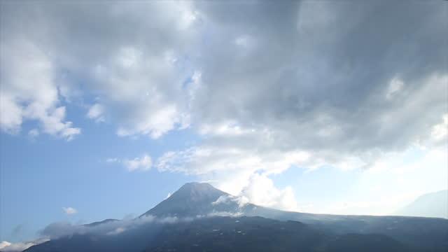 stockvideo's en b-roll-footage met tijd lapse weergave van wolken passeren boven de top van de vulkaan - ecuador