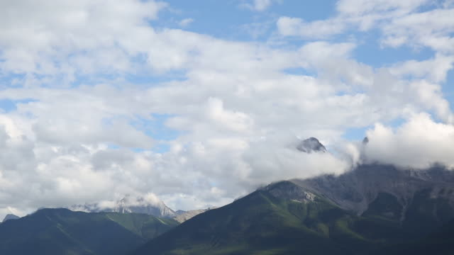 time lapse view of clouds passing overhead mountains - sunny stock videos & royalty-free footage