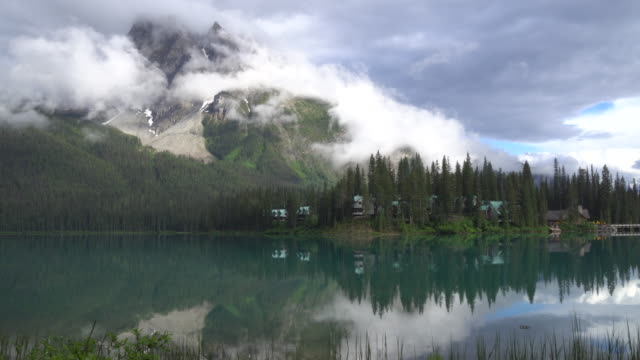 Time lapse view of clouds rising above mountain lake