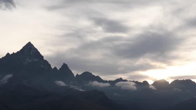 vidéos et rushes de vue de laps de temps des nuages coulant au-dessus de la crête au lever de soleil - mauvais présage