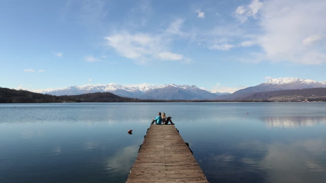Time lapse view of couple on dock protruding into lake