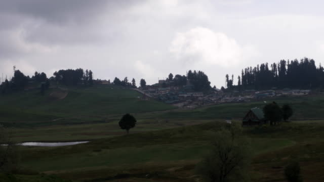 A time lapse view of fast moving thunder clouds gathering over Gulmarg town and the central golf course in the meadows