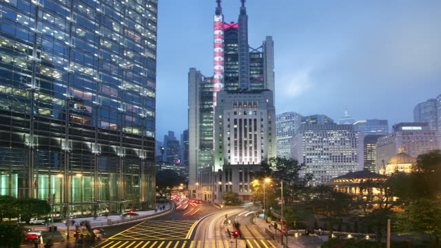 Time lapse view of HSBC Building lighting up and traffic on Hennessy Road passing Charter Garden from dusk to night / view of The Center in background / Hong Kong