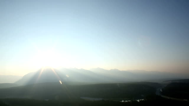 Time lapse view of mountains and sunrise over lake