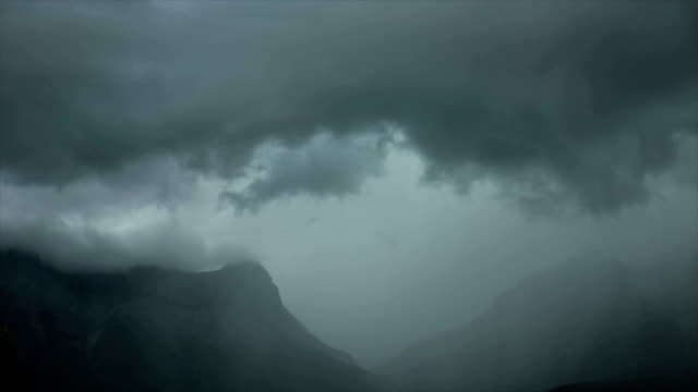 Time lapse view of storm clouds above mountains