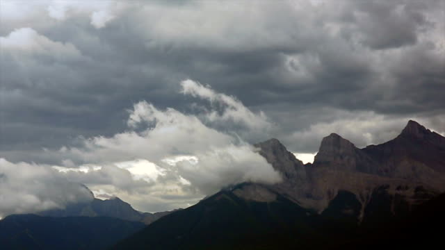 Time lapse view of storm clouds building above mountains