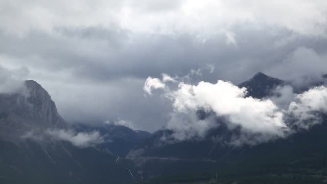 Time lapse view of storm clouds passing overhead mountains