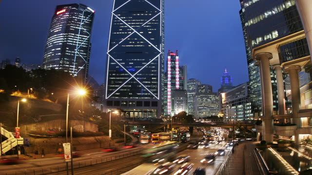 time lapse view of traffic on hennessy road passing bank of china tower and hsbc building at night / view of the center in background / hong kong - bank of china tower hong kong bildbanksvideor och videomaterial från bakom kulisserna