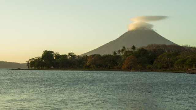 time lapse volcano and lake from sunset to dusk. concepcion, ometepe, nicaragua. we can see the lake cocibolca on the foreground and the mountain with a cloud that moves on spiral - nicaragua stock videos & royalty-free footage