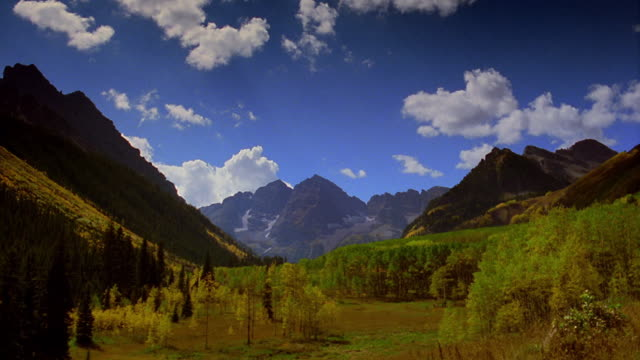 time lapse white fluffy clouds moving over valley surrounded by mountains / aspen, colorado - コロラド州点の映像素材/bロール