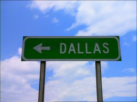 """time lapse white puffy clouds in blue sky behind """"Dallas"""" road sign"""