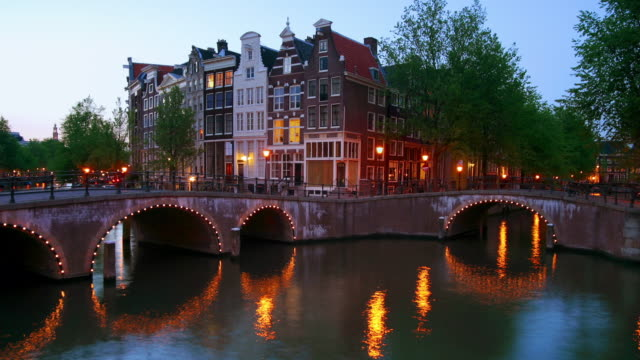 time lapse wide shot boats on the keizersgracht canal and pedestrians on quay at leidse square /twilight / amsterdam - amsterdam stock videos & royalty-free footage