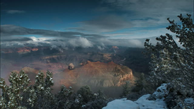 Time lapse wide shot clouds passing over Grand Canyon during snowstorm / Grand Canyon National Park, Arizona