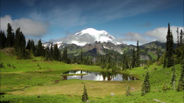 time lapse wide shot clouds passing over mount ranier / mount ranier national park, washington - mt rainier stock videos & royalty-free footage