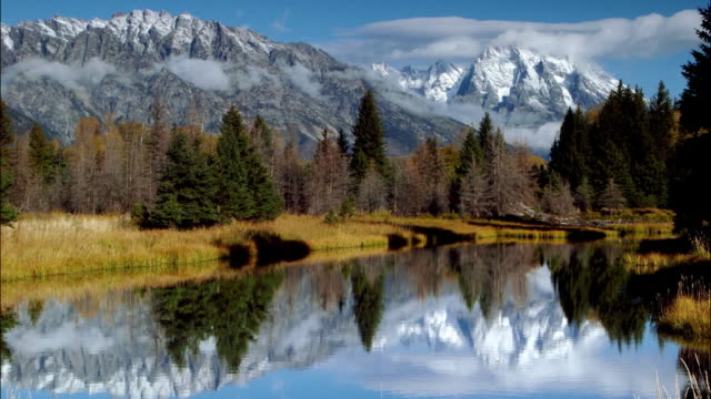 time lapse wide shot clouds passing over rocky mountains reflected in lake / grand teton national park, wyoming - grand teton national park stock videos & royalty-free footage