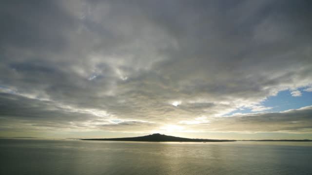 Time lapse Wide shot clouds rolling over  Rangitoto Island at dawn with boats floating in under golden light / Auckland, New Zealand.