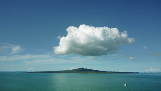 Time lapse Wide shot clouds rolling over  Rangitoto Island with boats floating in , Auckland, New Zealand.