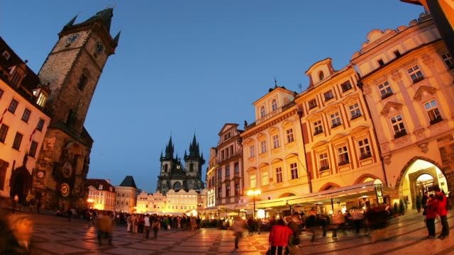 Time lapse wide shot crowd in Old Town Square / Church of Our Lady before Tyn in background / sky growing dark / Prague