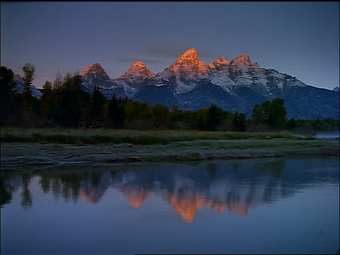vídeos de stock, filmes e b-roll de time lapse wide shot dawn over snowy grand teton mountains + forest / mist-covered jackson lake in foreground - grand teton