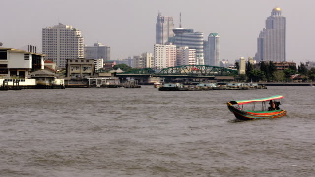 time lapse wide shot ferries on the chao phraya river with memorial bridge in background / bangkok, thailand - チャオプラヤ川点の映像素材/bロール
