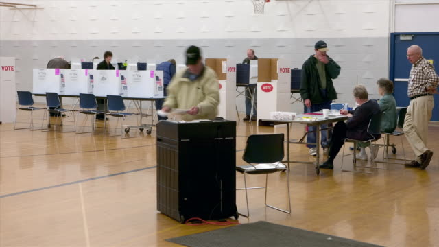 stockvideo's en b-roll-footage met time lapse wide shot lockdown men and women casting votes in ballot box in polling station in school gym ypsilanti, michigan, november 7, 2006 - stembus