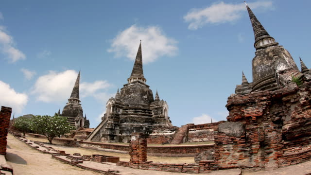 time lapse wide shot of clouds passing over pagodas of wat phra si sanphet at ayutthaya / thailand - アユタヤ県点の映像素材/bロール