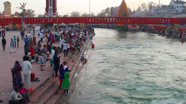 vídeos de stock, filmes e b-roll de time lapse wide shot of the bathing ghats on ganges' banks wth pilgrims at har ki pauri in haridwar, india - 2016