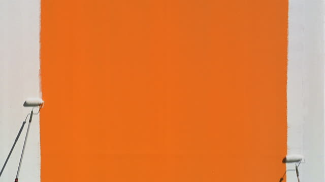 time lapse wide shot orange wall being painted white / green screen - paint roller stock videos & royalty-free footage