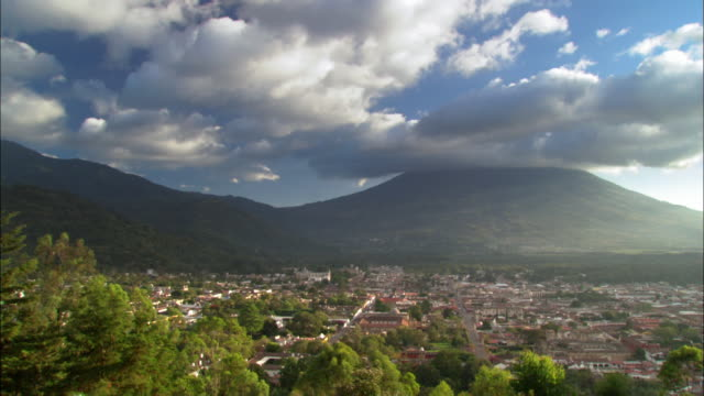 time lapse wide shot over town with mountains in background / antigua, guatemala - guatemala stock videos & royalty-free footage