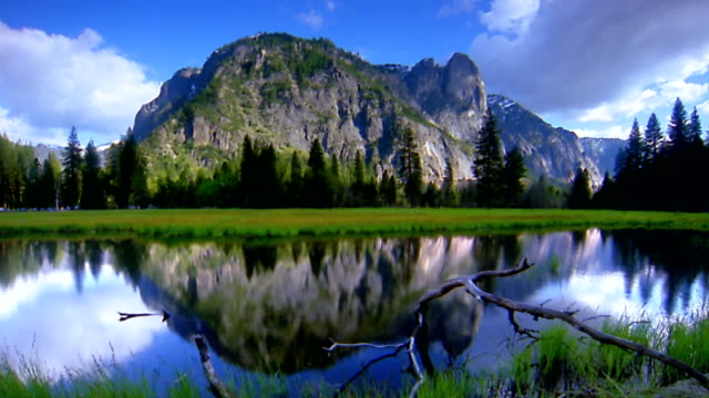 Time lapse wide shot pan lake with mountain and trees in background / Yosemite National Park, California