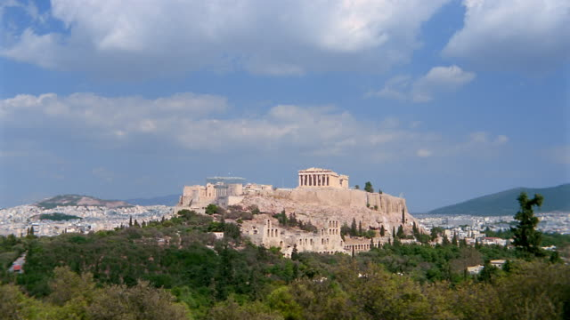 Time lapse wide shot Parthenon on the Acropolis under clouds and blue sky / Athens, Greece