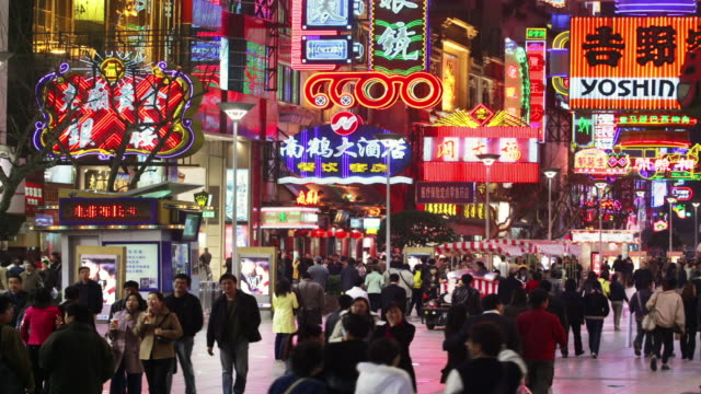 time lapse wide shot pedestrians walking past stores on nanjing road at night / shanghai - street light stock videos & royalty-free footage