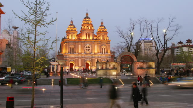 Time lapse wide shot people and traffic outside St. Joseph's East Church across Wangfujing / day to night / Beijing