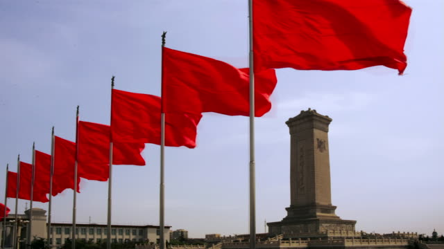 time lapse wide shot red flags waving near monument to the people's heroes at tiananmen square / beijing, china - tiananmen square stock videos and b-roll footage