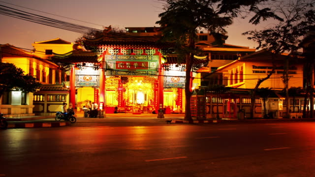 time lapse wide shot traffic and worshipppers outside buddhist temple in chinatown / dusk to night / bangkok, thailand - dusk to night stock videos & royalty-free footage