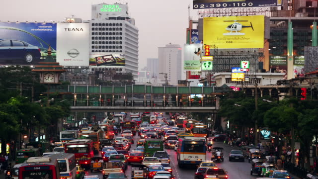 Time lapse wide shot traffic on the Rachadamri near the World Trade Center / dusk to night / Bangkok, Thailand